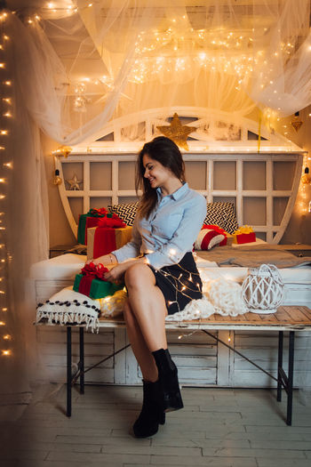 Full Length Real People One Person Young Women Sitting Indoors  Lifestyles Young Adult Women Leisure Activity Casual Clothing Seat Front View Adult Fashion Chair Hairstyle Table Beautiful Woman Flooring