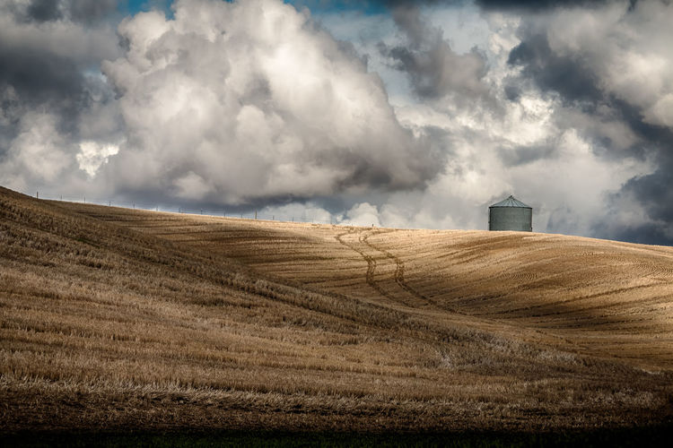 Distant View Of Silo On Agricultural Field Against Cloudy Sky