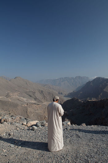 Rear view of man in traditional clothing standing on mountain against clear sky