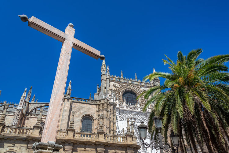 Large stone cross and palm trees in front of the gothic cathedral in Seville, Spain Seville Sevilla Architecture Built Structure Building Exterior No People Europe SPAIN Travel Travel Destinations Tourism Façade Medieval European  Spanish Church Cathedral Religion Catholicism Christianity Spirituality Building Cross Stone Palm Tree Gothic Gothic Architecture Sky Blue Clear Sky Tropical Climate Belief Tree