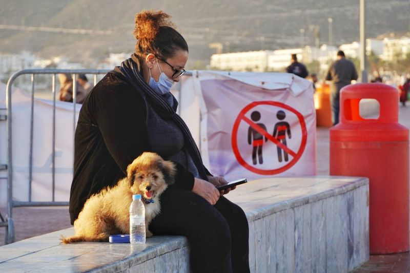 Woman using mobile phone with dog sitting outdoors