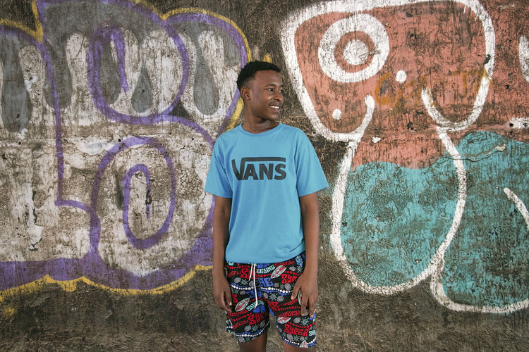 Young Adult Black Model Fashion Fashion Model Fashion Photography Vans Graffiti Graffiti Wall One Person Standing Front View Creativity Smiling Casual Clothing Wall - Building Feature Lifestyles Art And Craft Portrait Three Quarter Length Looking At Camera Day Teenager Child Happiness Boys Real People Outdoors Adolescence  Teenage Boys