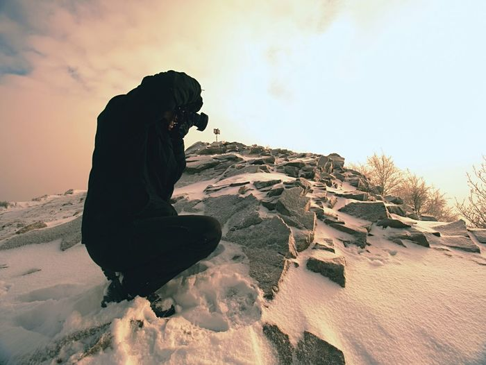 Photographer lay in snow on mountain peak and takes a picture of  landscape around, snowy winter day