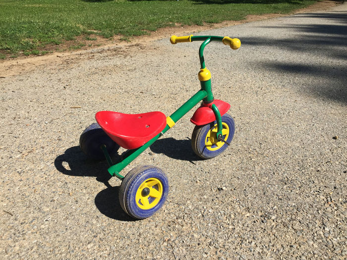 Day Grass Green Color Ground Multi Colored Nature No People Outdoors Parking Playground Stationary Sunlight Sunny Tranquility Tricycle Trike