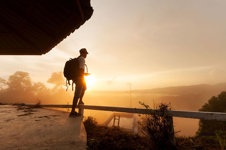 Man standing at observation tower against sky during sunset