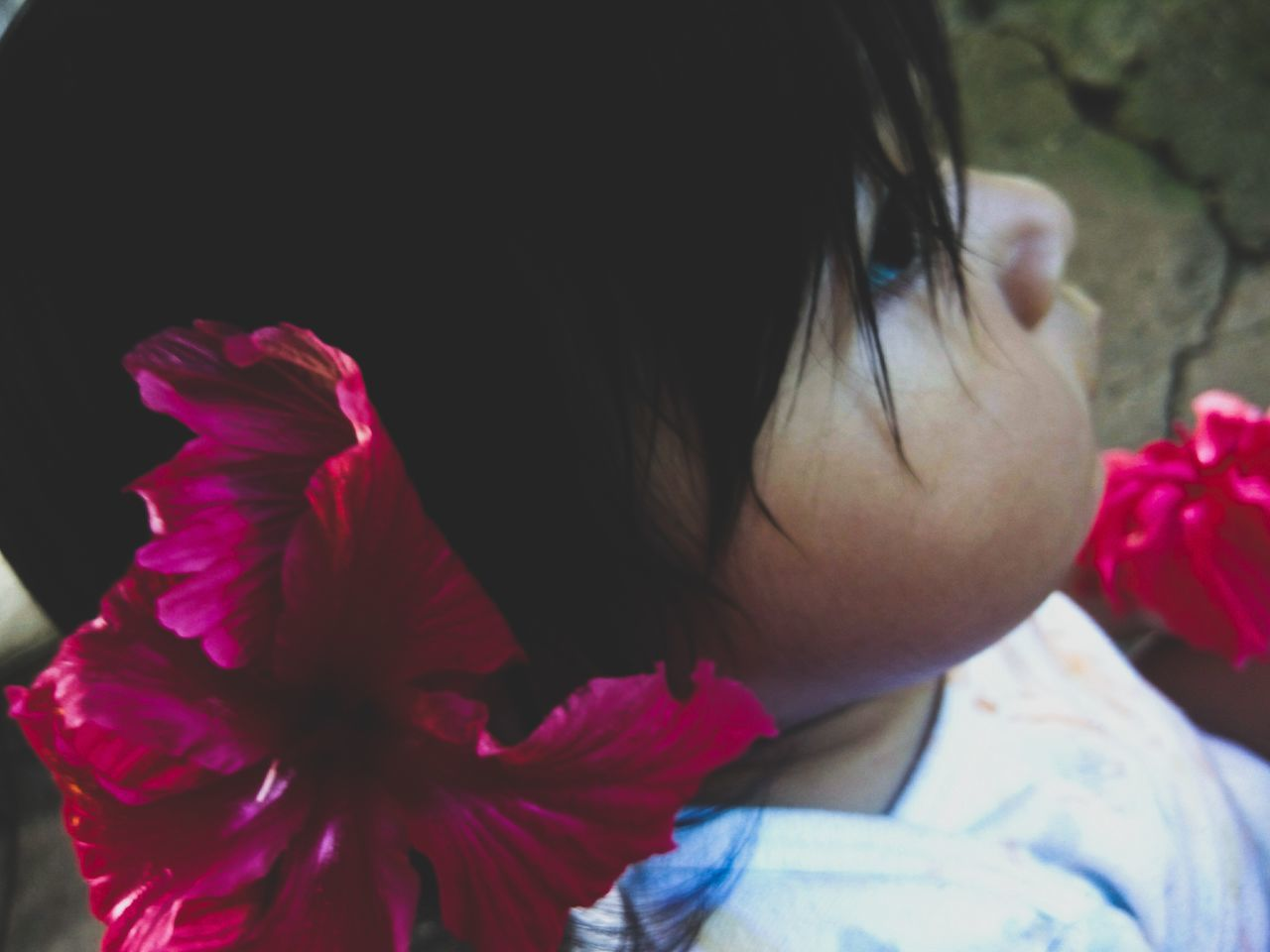 High Angle Close-Up Of Girl Wearing Hibiscus Flower While Sitting On Road