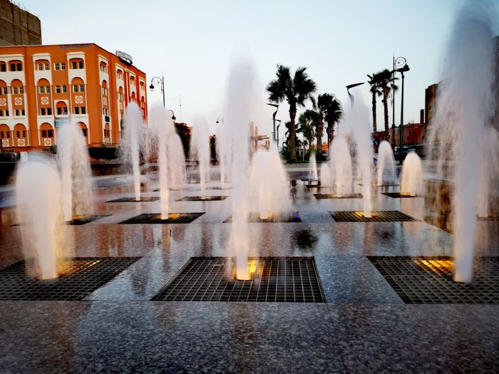 fountain at Laayoune city Lowlight Lowlightphotography Water Light Building Exterior Palm Tree Morocco MoroccoTrip Morocco 🇲🇦 EyeEm Selects City Water Spraying Destruction Fountain Sky Architecture