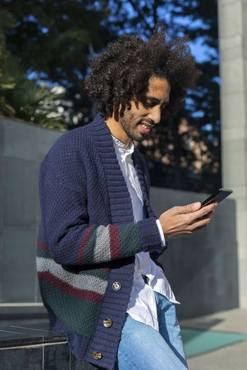 Young Man Using Phone While Leaning On Railing In City