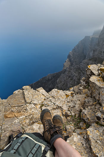 Woman with hiking boots admiring a view of the sea and rocky shore, the Aegean Sea, Amorgos Island, Greece Day Human Body Part Human Leg Leisure Activity Lifestyles Low Section Mountain Nature One Person Outdoors People Personal Perspective Real People Shoe Standing The Great Outdoors - 2017 EyeEm Awards