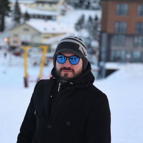Portrait of man wearing sunglasses standing in snow outdoors