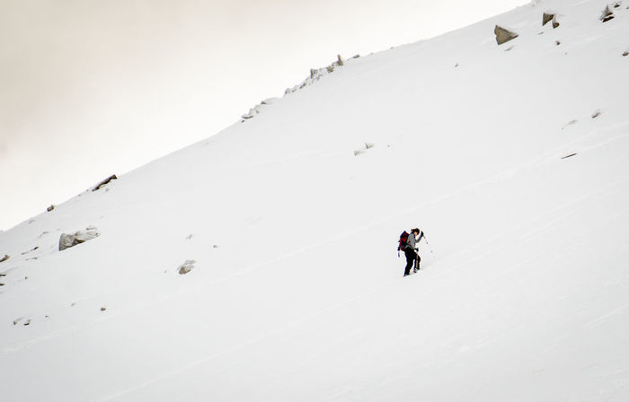 A woman skis up a mountain ridge on a cloudy day. Adventure Backcountry Carefree Copy Space Day Fun Mountaineering Mountains One Person Outdoors Recreational Pursuit RISK Skiing Unrecognizable Person Woman