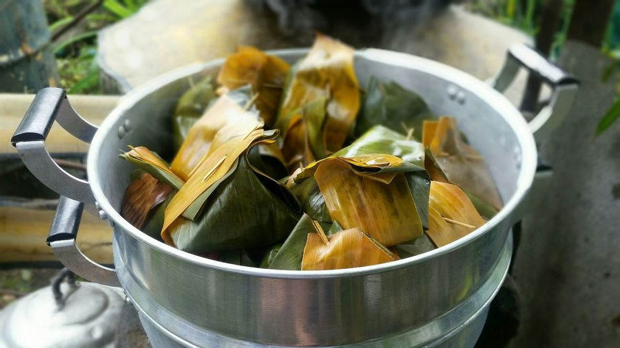 High Angle View Food Wrapped In Banana Leaf Being Cooked In Pan Outdoors