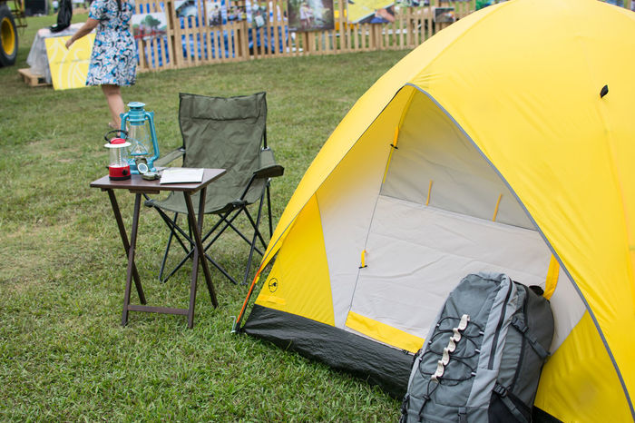 Yellow tent ,one backpack and Survival equipment set for exhibition tourism Adult Backpacker Camping Day Grass Leisure Activity Low Section Men Nature One Person Outdoors People Real People Survival Of The Fittest Tent Tent Camping Tourism