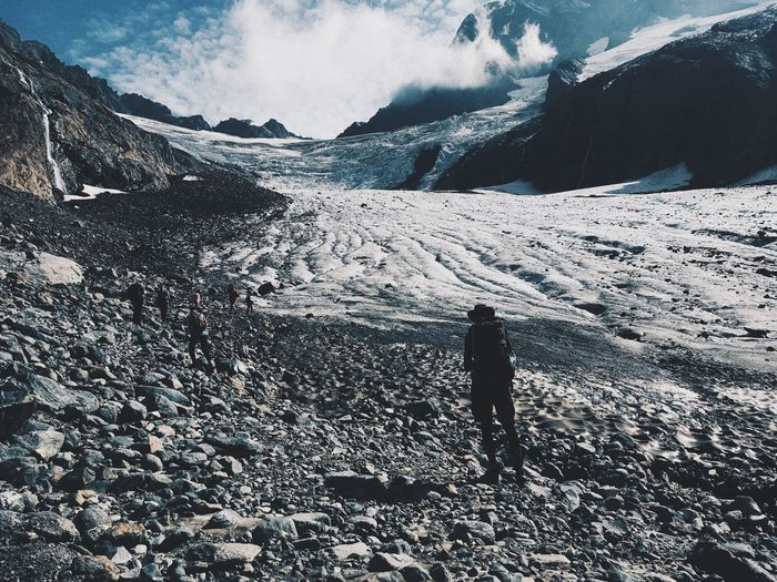Person walking on snowcapped mountain
