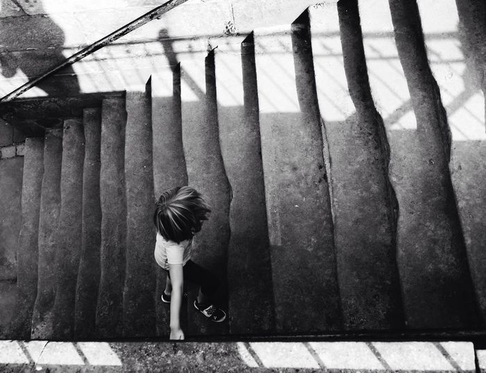 High angle view of child climbing stairs