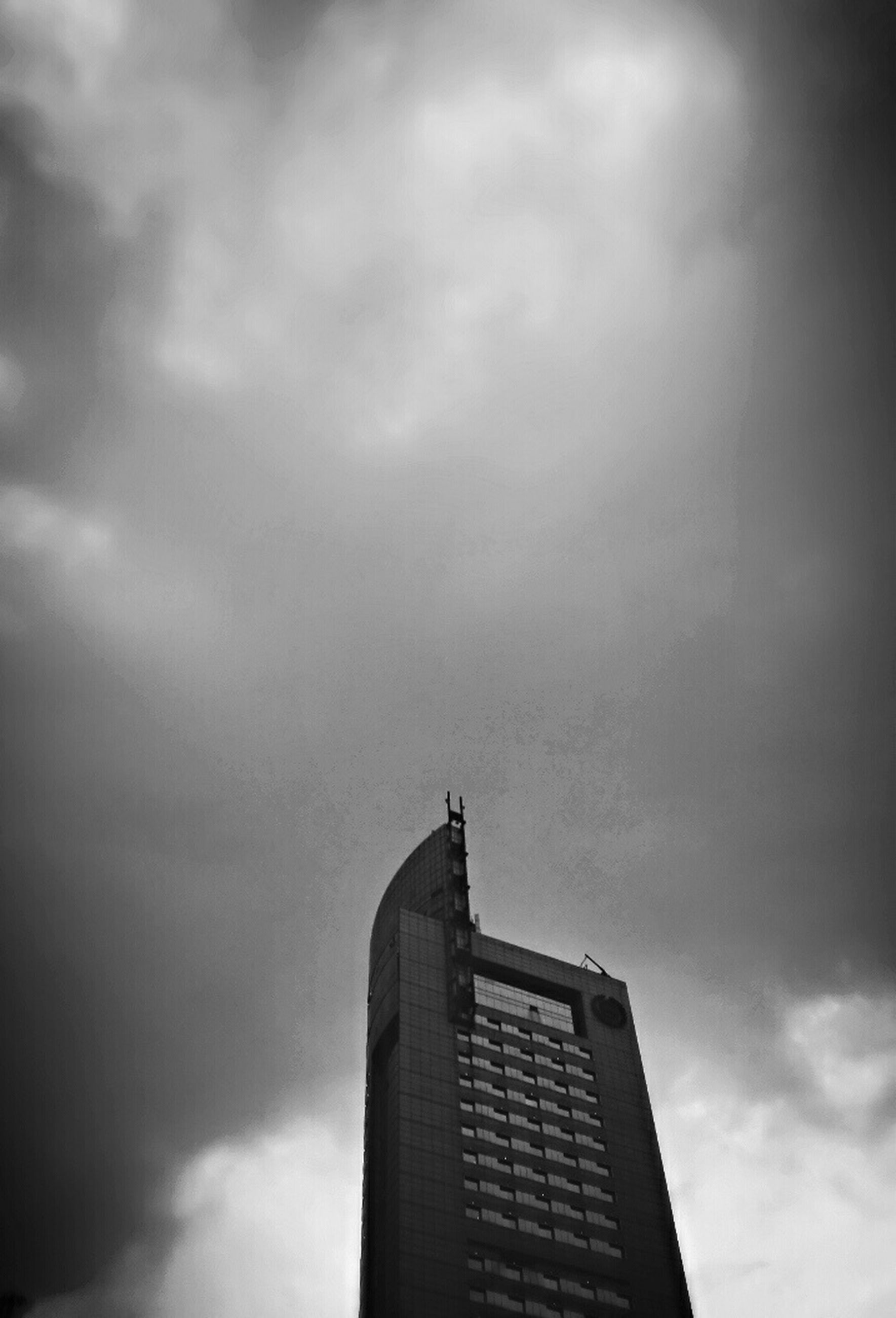 architecture, building exterior, built structure, low angle view, sky, cloud - sky, cloudy, city, building, overcast, weather, tall - high, tower, modern, cloud, office building, skyscraper, outdoors, day, high section