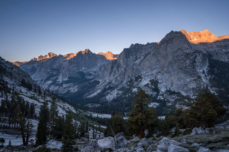 I could taste stillness | JMT DAY 19 - LE CONTE CANYON AT SUNRISE Le Conte Canyon at sunrise When I woke up, it was quite dark. It felt darker probably because our campsites were immersed in the forest. The tall pines hovering over us felt like giant creatures. As my lungs were busy filling up frigid air, I felt my fingers titillating as if they were stretching. Still adjusting to the dim surroundings, my eyes were slowly hunting for my gear inside the tent. Once reaching the trail, I traced it back down to where we came the day before. And soon I emerged from the forest and was greeted by the spectacular sight of Le Conte Canyon. Now, with a dose of newly charged eagerness, I scurried up the rocky slope, found a huge boulder as large as a mid-size SUV and climbed it. What unfolded before my eyes was the canyon, which had already taken my breath away the day before when we were coming down from Helen Lake, slowly waking up to the gorgeous hues of Earth's Shadow. I could taste the stillness. As if time stood still. As if nothing mattered after that moment. My mind was surely harnessing the inspiration of the stillness. I was about to buoy up into the air. Soon, the ridges and the Citadel (11,748 ft) were painted in bright orange while the ambient light was slowly flooding the entire canyon. Le Conte Canyon, Kings Canyon National Park, CA Mountain Beauty In Nature Scenics - Nature Tranquil Scene Sky Tranquility Landscape Cold Temperature Nature Mountain Range Tree Idyllic No People Non-urban Scene Plant Outdoors Mountain Peak Formation Sunrise Sunrise Glow Le Conte Canyon Kings Canyon National Park Pct TheCity Adventure