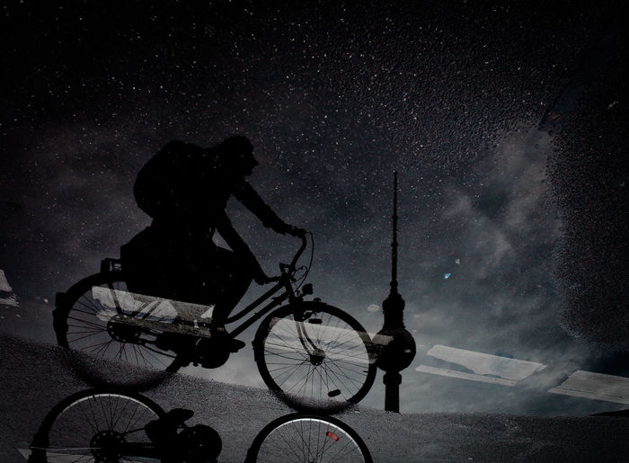 Man riding bicycle on street against sky at night