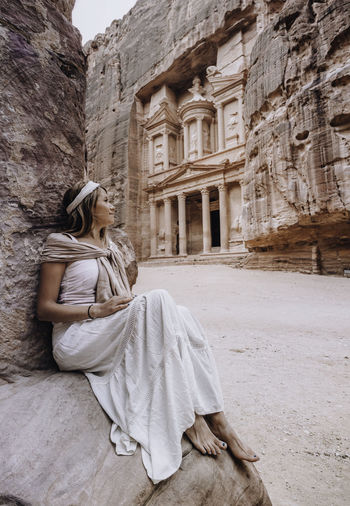 Woman sitting on rock against historic building