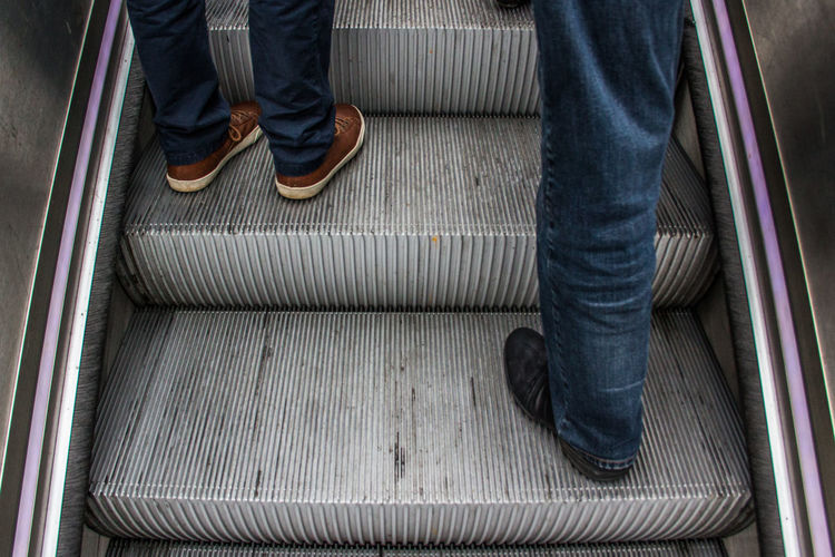 Low Section Of Men Standing On Escalator