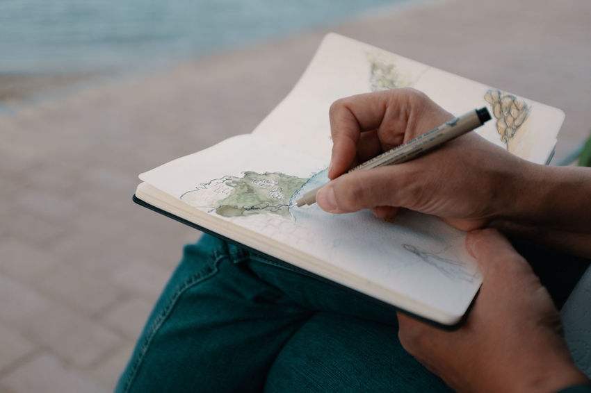 One Person Human Hand Holding Real People Hand Human Body Part Focus On Foreground Leisure Activity Day Lifestyles Men Water Pen Close-up Paper Unrecognizable Person Sitting High Angle View Outdoors Finger Sketching Sketchbook Fourdayspalma