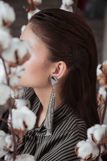 Close portrait of unrecognizable woman with earring  with cotton flower heads as background