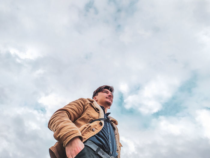 Low angle view of man standing against cloudy sky