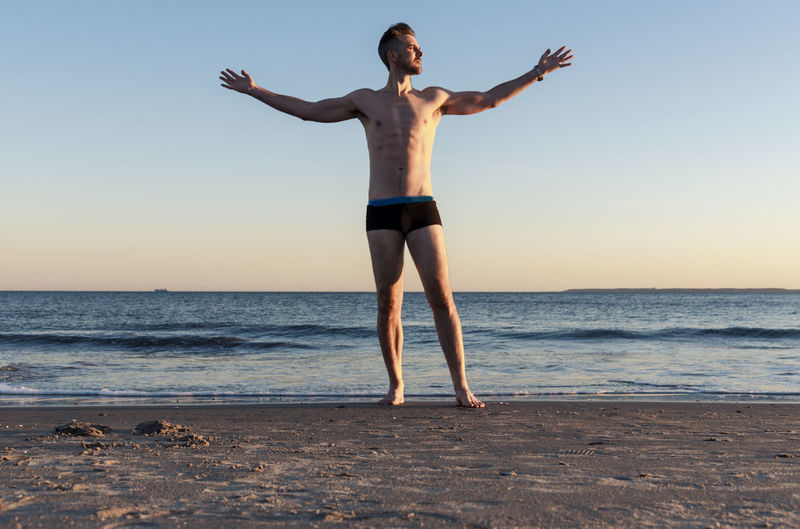Man with raised arms at the beach near sunset lit by sun. Sky Sea Water Beach Land Lifestyles Full Length Horizon Standing Horizon Over Water Leisure Activity Human Arm One Person Beauty In Nature Sunset Nature Limb Outdoors Arms Raised Healthy Eating Fitness Exercise Male Model Handsome Caucasian