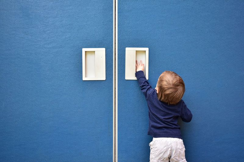 Rear view of boy standing against blue wall