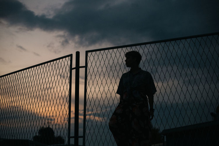 Silhouette woman standing by fence against sky during sunset