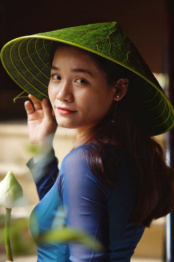 Portrait of young woman holding hat