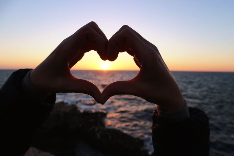 Close-up of hand holding heart shape against sky at sunset