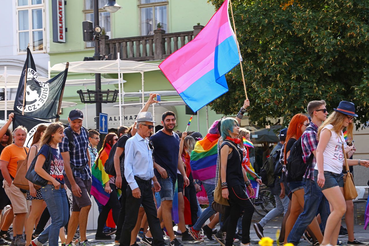 real people, large group of people, day, outdoors, casual clothing, flag, men, women, togetherness, building exterior, lifestyles, multi colored, architecture, city, crowd, adult, people