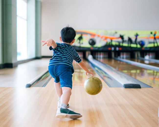 back view child throwing bowling ball Ball Bowling Boy Boys Casual Clothing Child Childhood Flooring Focus On Foreground Full Length Hairstyle Indoors  Innocence Kid Leisure Activity Lifestyles Males  Men Motion One Person Pin Playing Real People Rear View Sport