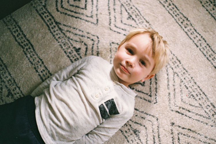 High angle portrait of smiling boy lying on floor