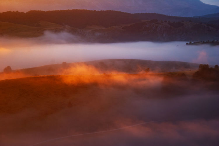 Aerial view of foggy landscape during sunset