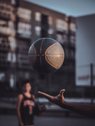 Cropped image of man with ball against building in city