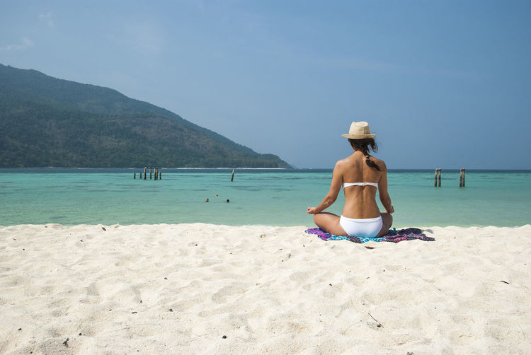 Rear view of a woman meditating on beach