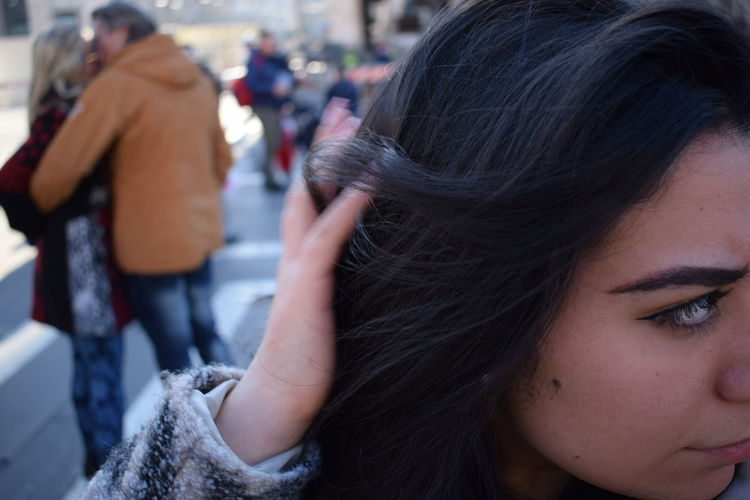 Close-up of young woman with hand in hair looking away