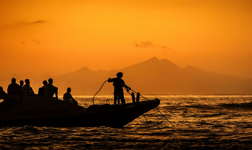 Boat as traditional transportation at Bali,Indonesia. A mountain as backgrounds view taken during sunrise or sunset. Orange Sky Beauty In Nature Boat Day Golden Hour Leisure Activity Lifestyles Medium Group Of People Men Mountain Mountains Nature Nautical Vessel Orange Color Outdoors People Real People Scenics Sea Silhouette Sky Sunset Traditional Transportation Water