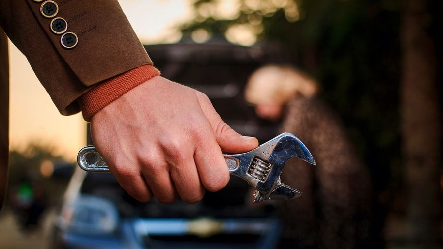 Cropped hand of man holding wrench