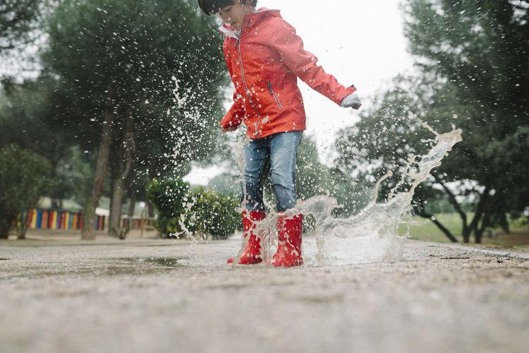 Full length of man splashing water in park