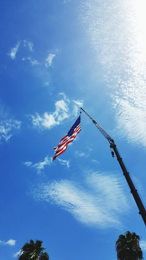 Low Angle View Of American Flag Hanging From Crane Against Sky