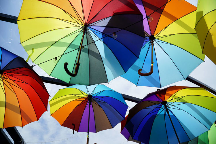 Low angle view of umbrellas hanging against sky