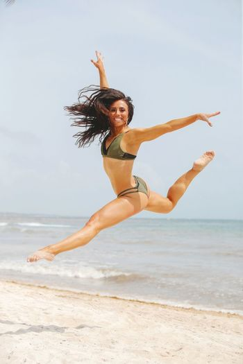 Young woman with arms raised on beach against sky