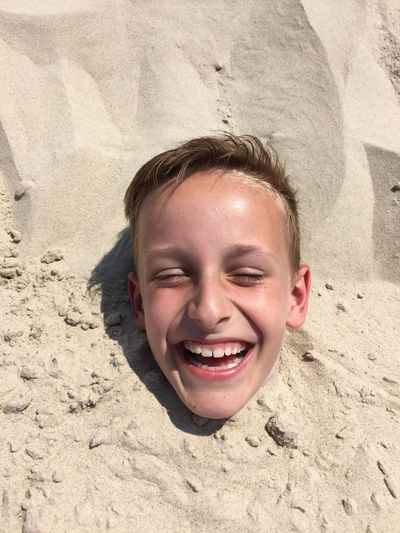 Portrait of boy buried up to his neck in sand on beach