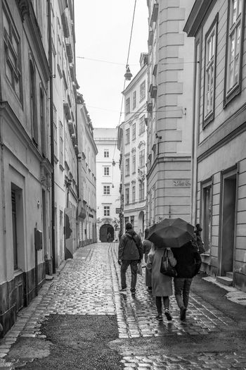 Adult Alley Architecture Building Building Exterior Built Structure City Day Direction Footpath Full Length Men Outdoors Rain Rainy Season Real People Rear View Street The Way Forward Umbrella Walking Wet