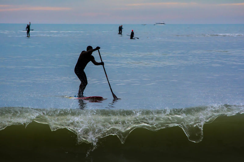 Silhouette Mid Adult Man Paddleboarding On Sea Against Cloudy Sky During Sunset