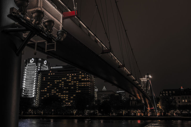 Low angle view of illuminated bridge over river and buildings at night