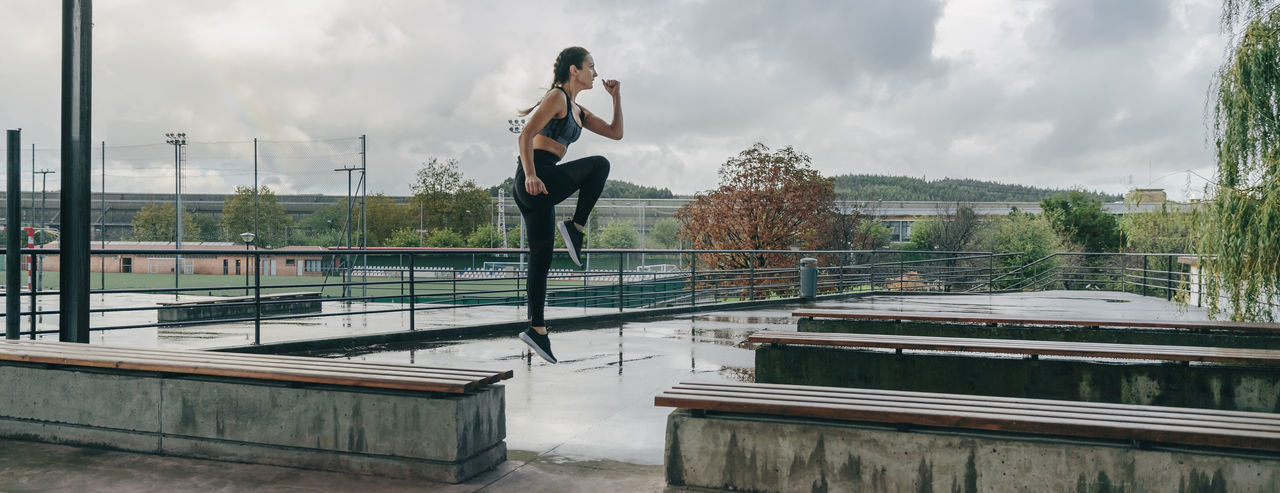 Full length of woman on railing against sky